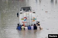 FILE - Men push a truck through a flooded road during monsoon rain, in Karachi, Pakistan, Aug. 25, 2020.