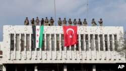 Turkiya askarlari va Turkiya himoyasidagi muxolif jangchilar bino tepasida, Ras al-Ayn, Suriya, 2019-yil, 23-oktabr