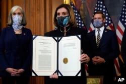 La presidenta de la Cámara de Representantes, Nancy Pelosi, muestra el artículo de juicio político firmado contra el presidente Donald Trump en una ceremonia antes de transmitirlo al Senado para su juicio el 13 de enero de 2021.