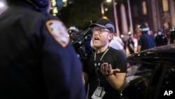"""Gazetari Robert Bumsted duke i kujtuar punonjësit të policisë se reporterët konsiderohen """"punonjës thelbësorë"""" dhe lejohen në rrugë edhe gjatë shtetrrethimit (2 qershor 2020, Nju Jork)"""
