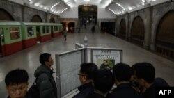 북한 평양의 지하철역에서 행인들이 로동신문을 읽고 있다.