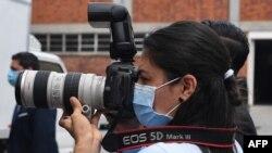 Una fotoperiodista usa una máscara quirúrgica durante una conferencia de prensa en San Salvador, el 21 de abril de 2020.