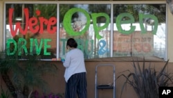 Lucy Kwak paints a sign on the window of a fast-food chain's restaurant indicating that the drive-through window is still open as well as a takeout option during the coronavirus outbreak in Garden Grove, Calif., March 26, 2020.