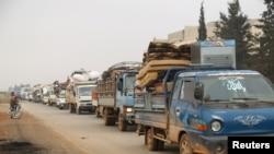 FILE - Trucks carry belongings of people fleeing from Maaret al-Numan, in northern Idlib, Syria, Dec. 24, 2019.
