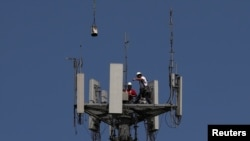 Workers install 5G telecommunications equipment on a T-Mobile tower in Seabrook, Texas, May 6, 2020.
