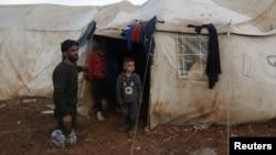 បុរសម្នាក់ឈរនៅជិតកូនរបស់លោកនៅខាងក្រៅតង់មួយនៅជំរំជនផ្លាស់ប្ដូរលំនៅក្នុងស្រុក នៅភាគខាងជើងខេត្ត Aleppo ក្បែរព្រំប្រទល់រវាងប្រទេសស៊ីរី និងប្រទេសតួកគី ថ្ងៃទី១៧ ខែកុម្ភៈ ឆ្នាំ២០២១។