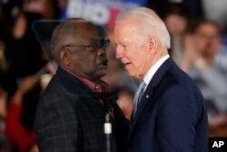 Democratic presidential candidate former Vice President Joe Biden talks to Rep. James Clyburn, D-S.C., at a primary night election rally in Columbia, S.C., Feb. 29, 2020 after winning the South Carolina primary.