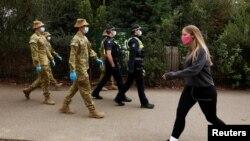 Petugas ADF dan polisi Victoria melakukan patroli saat diberlakukannya pembatasan di Melbourne, Australia, 26 Juli 2020. (AAP Image/Daniel Pockett via Reuters)