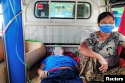 A relative sits with a COVID-19 patient being taken to hospital in the town of Kale, Sagaing region, Myanmar, July 6, 2021.