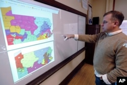 William Marx points to old GOP-drawn Pennsylvania districts (top), which were struck down by a Democratic-majority state Supreme Court, and new re-drawn districts (bottom) in his Pittsburgh classroom, Nov. 16, 2018.