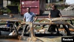 在威斯康辛州基諾沙的警察槍擊黑人男子佈雷克引發抗議後,人們站在當地被破壞的一處二手車場前。(2020年8月27日)