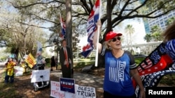 Former U.S. President Donald Trump supporter Kelly Fitzer waves a flag outside of the Conservative Political Action Conference (CPAC) in Orlando, Florida, U.S., Feb. 28, 2021.