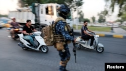 Men ride motorbikes past a member of Iraqi federal police in a street in Baghdad, Iraq October 7, 2019.