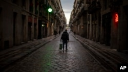 A man walks along an empty street in downtown Barcelona, Spain