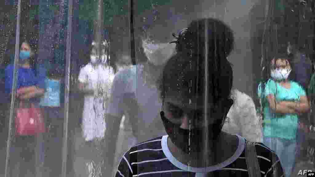 스리랑카 콜롬보에서 여성이 건물 앞에 설치된 대인 소독부스를 지나고 있다.