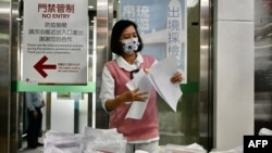 FILE - A staff member checks documents on COVID-19 coronavirus tests at Taoyuan International Airport near Taipei on April 1, 2021, before tourists head to Palau as part of a travel bubble plan.