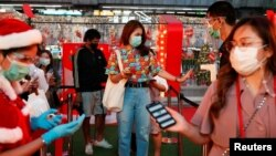 People check their temperature as they visit the Christmas light festival in Bangkok, Thailand, Dec. 21, 2020.
