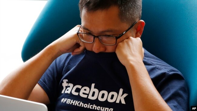 Facebook staff member looks at his computer after the opening ceremony of the company's new office in Hong Kong, July 24, 2014.
