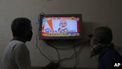 រូបឯកសារ៖ មនុស្សពីរនាក់ពីការថ្លែងសុន្ទរកថាតាមទូរទស្សន៍របស់លោកនាយករដ្ឋមន្រ្តី Narendra Modi ពាក់ព័ន្ធនឹងផែនការជំរុញសេដ្ឋកិច្ច នៅក្រុង Hyderabad ប្រទេសឥណ្ឌា កាលពីថ្ងៃទី១២ ខែឧសភា ឆ្នាំ២០២០។