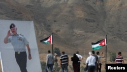 FILE - Jordanian visitors walk next to a poster depicting Jordanian King Abdullah during their visit to Baquora area in Jordanian border side, in the border area between Jordan and Israel, Nov. 13, 2019.