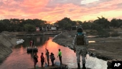 A Mexican National Guard looks at local residents crossing the Suchiate River, near Ciudad Hidalgo, on the Mexican border with Guatemala, Jan. 17, 2020.