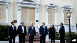 President Donald Trump stands outside St. John's Church, June 1, 2020, in Washington. Standing with Trump are Mark Esper, from left, William Barr, Robert O'Brien, Kayleigh McEnany and Mark Meadows.