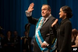 FILE - Alejandro Giammattei, accompanied by his daughter, Ana Marcela, waves to the crowd after he was sworn in as president of Guatemala at the National Theater in Guatemala City, Jan. 14, 2020.