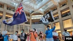 Activists chant slogans, display a British colonial flag and banners at a protest in Landmark shopping mall, June 9, 2020. (Verna Yu/VOA)