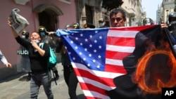 Prosvjednici protiv peruanskog predsjednika Martina Vizcarre, koji se suočava s opozivom, nose američku zastavu s slovom Q, pozivajući se na QAnon, u blizini Kongresa u Limi, Peru, 9. novembra 2020.