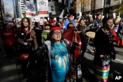 People taking part in a rally to mark Indigenous Peoples' Day in downtown Seattle sing as they march toward Seattle City Hall, Monday, Oct. 14, 2019. The observance of the day was made official by the Seattle City Council in 2014.