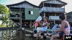 Warga di Leticia, Kolombia mencuci pakaian mereka di tepi sungai Amazon, 13 Mei 2020. Pemerintah Kolombia memperketat restriksi di kawasan ini, untuk menghentikan kenaikan jumlah kasus baru virus corona, Kamis malam (14/5).