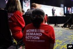 "Audience members wearing ""Moms Demand Action"" gun reform T-shirts listen to Democratic presidential candidate Sen. Michael Bennet speak at the Presidential Gun Sense Forum, Aug. 10, 2019, in Des Moines, Iowa."