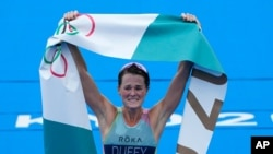 Flora Duffy of Bermuda celebrates after crossing the finish line to win the gold medal in the women's individual triathlon competition at the 2020 Summer Olympics, July 27, 2021, in Tokyo, Japan.