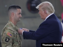 U.S. President Donald Trump awards the Distinguished Flying Cross to California National Guard Sergeant Cameron Powell during a ceremony to honor Powell and six other helicopter crew members at McClellan Park, California, Sept. 14, 2020.