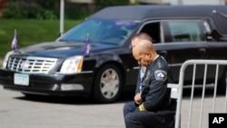 미국 미네소타주 미니애폴리스에서 경관들이 4일 조지 플로이드 시신을 운구한 차량이 도착하자 무릎을 끓고 있다.