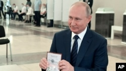 Russian President Vladimir Putin shows his passport to a member of an election commission as he arrives to take part in voting at a polling station in Moscow, Russia, July 1, 2020.