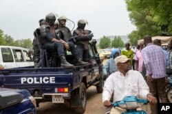 FILE - Malian police gather outside the Bourse du Travail where striking workers gathered to protest the arrest of President Bah N'Daw and Prime Minister Moctar Ouane by military personnel in Bamako, Mali, May 25, 2021.