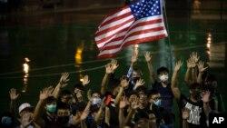 Para demonstran pro-demokrasi di Hong Kong melambaikan bendera Amerika dalam aksi protes hari Selasa (15/10).