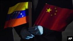 El canciller de Venezuela, Jorge Arreaza, sostiene las banderas de Venezuela y China mientras llegan especialistas médicos y suministros de China al Aeropuerto Internacional Simón Bolívar. en La Guaira, Venezuela. Marzo 30, 2020.