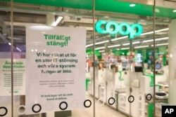"""FILE - A sign reads: """"Temporarily Closed. We have an IT-disturbance and our systems are not functioning"""", posted in the window of a closed Coop supermarket store in Stockholm, Sweden, July 3, 2021."""