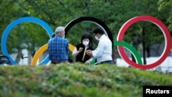 People chat next to Olympic Rings monument outside the Japan Olympic Committee (JOC) headquarters near the National Stadium, the main stadium for the 2020 Tokyo Olympic Games that have been postponed to 2021, in Tokyo, June 23, 2021. June…