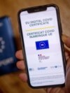 A picture taken on June 29, 2021 in Paris shows a passport behind a mobile phone whose screen bears a EU Digital COVID certificate.