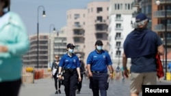 Police officers patrol the boardwalk at Long Beach on the first day that New York beaches were opened ahead of the Memorial Day weekend following the outbreak of the coronavirus pandemic, on Long Island, New York, May 22, 2020.