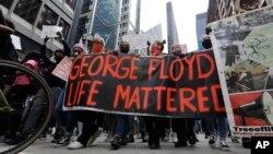 Warga memegang spanduk saat berdemo memprotes kematian George Floyd akibat kebrutalan polisi, d Chicago, Illinois, 30 Mei 2020.