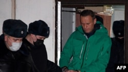 Pemimpin oposisi Rusia, Alexei Navalny, dikawal keluar dari kantor polisi di Khimki, di luar kota Moskow, Senin, 18 Januari 2021.