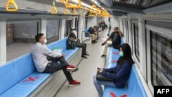 People sit on areas designated by red cross marks to ensure social distancing inside a light rapid transit train in Palembang, South Sumatra, Indonesia.