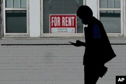 FILE - A man walks in front of a For Rent sign in a window of a residential property in San Francisco, Oct. 20, 2020.