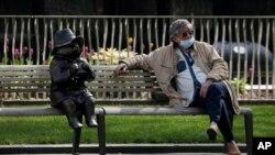 지난 15일 영국 런던에서 노년 남성이 패딩턴 곰 동상 옆에 앉아 있다.