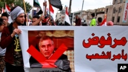 """Protesters hold a poster showing Iraq's Prime Minister-designate Mohammed Tawfiq Allawi with Arabic that reads, """"Rejected by order of the people,"""" during a rally in Baghdad, Iraq, March 1, 2020."""