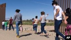 지난 6월 미국 애리조나주 유마의 미국-멕시코 국경장벽 틈을 통해 미국으로 불법 입국하는 브라질 출신 이민자들.
